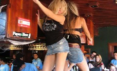 Two naughty and wild chicks get up on the table and dance l