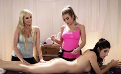 Two masseuses licking with their client on massage table